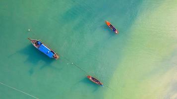 vista aerea dall'alto, barca da pesca, barca turistica che galleggia su un mare limpido poco profondo, bella acqua blu brillante nell'oceano foto
