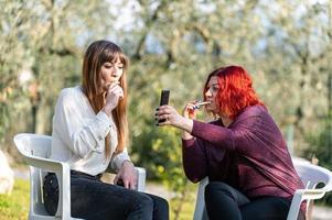 amiche che usano smartphone e fumano sigarette foto
