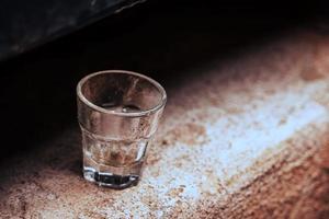 piccolo bicchiere vuoto in piedi da solo su una superficie di cemento foto