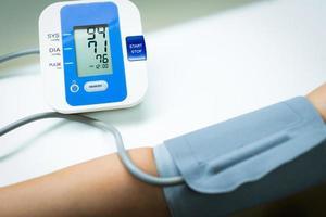 una dottoressa sta misurando la pressione sanguigna del paziente che ha l'ipertensione utilizzando un dispositivo automatizzato nella clinica dell'ospedale. concetto medico e sanitario foto