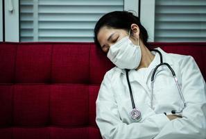dottore che dorme sul divano con indosso la maschera foto