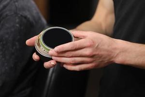 mani maschili che tengono una crema con un coperchio nero foto