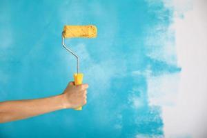 primo piano della mano femminile che tiene il rullo di vernice gialla su sfondo blu foto