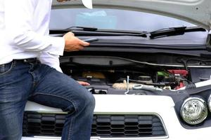 giovane asiatico seduto su un'auto rotta che chiede assistenza e ripara i veicoli a ruote sulla strada, sostituendo i pneumatici invernali ed estivi. concetto di sostituzione degli pneumatici stagionali foto