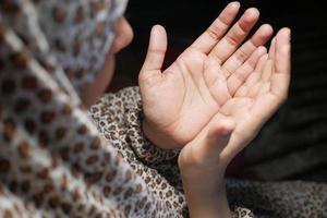 vista posteriore della mano delle donne musulmane che prega di notte foto