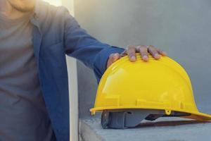 architetto lavoratore che tiene casco giallo nella costruzione di edifici foto