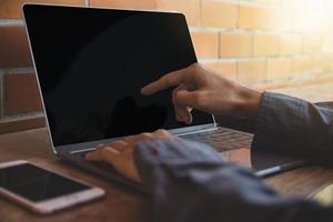 mano ravvicinata utilizzando la tecnologia del computer portatile foto