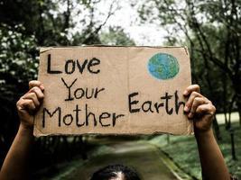 una volontaria con in mano un cartello di conservazione della natura si erge tra la natura della foresta. il concetto di giornata mondiale dell'ambiente foto