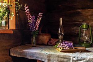 natura morta di oggetti vintage e un mazzo di lupini su un tavolo foto