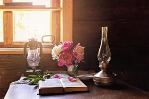 natura morta di oggetti vintage e un bouquet di peonie su un tavolo vicino alla finestra foto