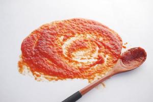salsa di pomodoro e cucchiaio di legno su sfondo bianco foto