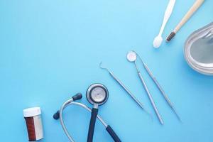 attrezzatura dentale, stetoscopio e contenitore per pillole su sfondo blu foto