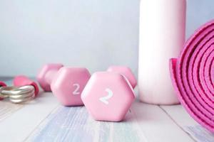 manubrio di colore rosa, tappetino per esercizi e bottiglia d'acqua su sfondo bianco foto