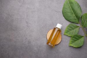 oli essenziali di eucalipto in una bottiglia di vetro con foglia verde su sfondo scuro foto