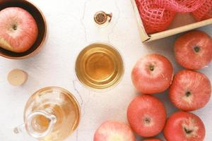 aceto di mele in bottiglia di vetro con mela rossa fresca sul tavolo foto