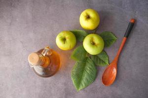 aceto di mele in bottiglia e mele verdi sul tavolo foto