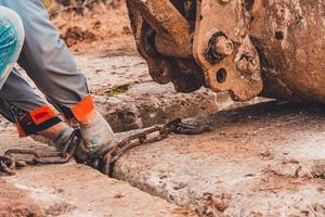 l'operaio aggrappa la catena alla benna dell'escavatore per sollevare la soletta di cemento. foto