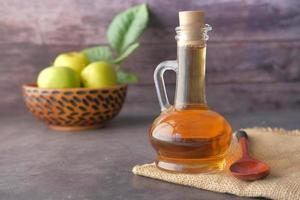 aceto di mele in bottiglia di vetro con mele verdi fresche sul tavolo foto