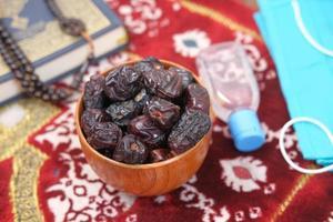 frutta fresca di dattero in una ciotola, rosario di preghiera, disinfettante per le mani e maschera sul pavimento foto