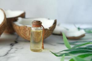fetta di cocco fresco e bottiglia di olio su un tavolo foto