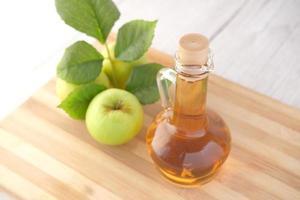 aceto di mele in bottiglia di vetro con mela verde fresca sul tavolo foto