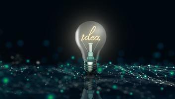 lampadina incandescente con la parola idea sullo sfondo della tecnologia aziendale digitale foto