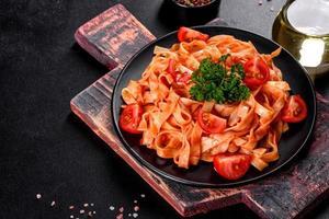 deliziosa pasta fresca con salsa di pomodoro con spezie ed erbe aromatiche su sfondo scuro foto