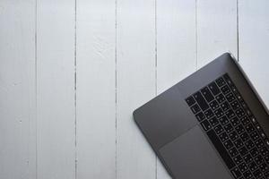 vista dall'alto del computer portatile su sfondo di legno bianco foto