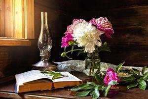 natura morta di oggetti vintage e un bouquet di peonie su un tavolo foto