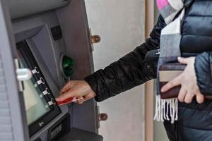 le mani femminili tengono una carta di credito bancaria di plastica, usano un bancomat foto