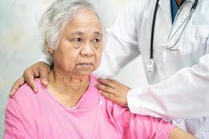 medico fisioterapista infermiere asiatico che tocca paziente donna anziana o anziana asiatica anziana con amore, cura, aiuto, incoraggiamento ed empatia nel reparto ospedaliero di cura, concetto medico sano e forte. foto