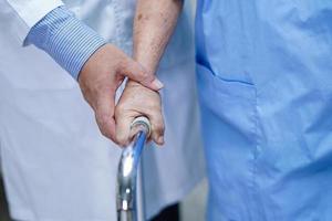 il medico aiuta il paziente asiatico anziana o anziana donna anziana a camminare con il deambulatore nel reparto ospedaliero di cura. foto