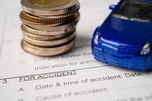 auto e monete sullo sfondo del modulo di assicurazione auto incidente, prestito auto, finanza, risparmio di denaro, assicurazione e concetti di tempo di leasing foto