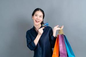 bella donna asiatica con borse della spesa e mostrando la carta di credito foto