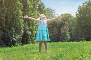 bambina con le braccia aperte, nel parco vita e natura foto