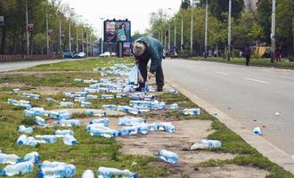 belgrado, serbia, 22 aprile 2017 - donna che raccoglie bottiglie d'acqua gettate via dopo la maratona foto