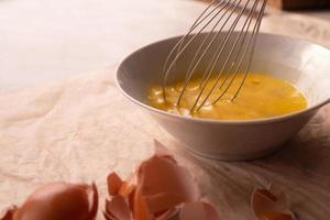 sbattere le uova in un piatto con una frusta foto