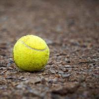 pallina da tennis gialla a terra foto