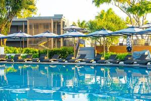 ombrellone e lettino intorno alla piscina all'aperto nel resort dell'hotel per le vacanze di viaggio foto