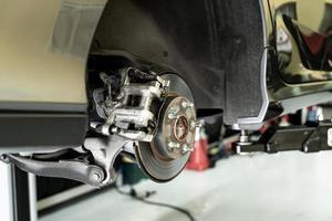 primo piano dell'auto a disco - meccanico che svita le parti dell'automobile mentre si lavora sotto un'auto sollevata foto