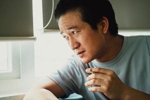 l'uomo asiatico si sente disperato per la dipendenza dal fumo foto