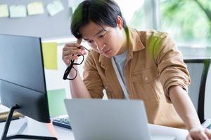 uomo d'affari asiatico che lavora con il computer in ufficio foto