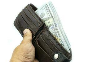mano che tiene portafoglio su fasci di banconote da 100 dollari USA su sfondo bianco foto