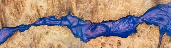 pannello in resina epossidica blu colata con legno di radica di noce, vista dall'alto del legno per lo sfondo foto