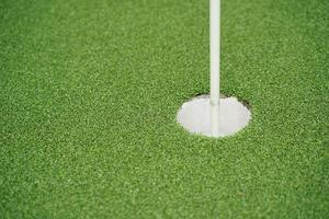 buca da golf e bandiera con l'erba verde, messa a fuoco selettiva. foto