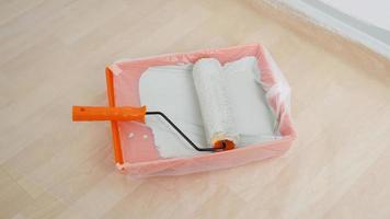 rullo di vernice in un coperchio del vassoio con un sacchetto di plastica. riparazione, nuova casa, tinteggiatura delle pareti. foto