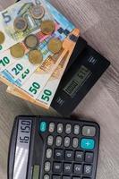 denaro in euro di diverse denominazioni su una scala calcolatrice foto