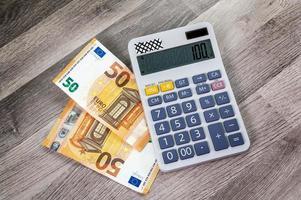Banconote da 50 euro con calcolatrice nelle vicinanze foto
