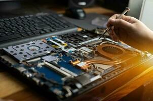 tecnico che ripara un computer portatile rotto con un cacciavite foto