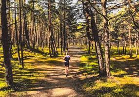persona caucasica che corre sul sentiero nel bosco foto
